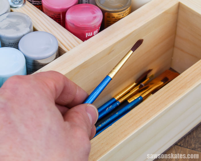 Hand removing a paintbrush from a DIY craft paint storage organizer