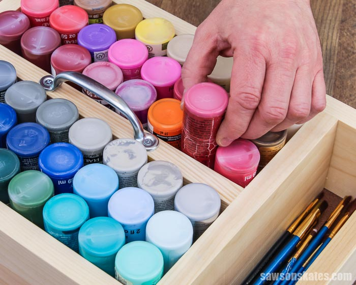 Hand removing a 2 oz paint bottle from a DIY craft paint storage caddy