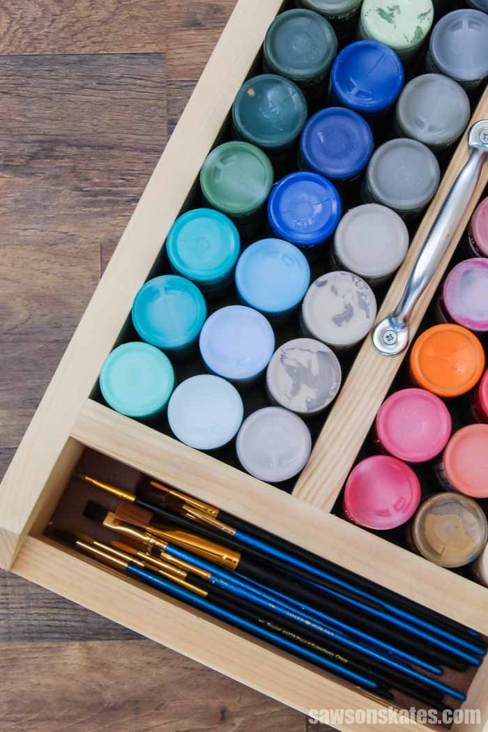Acrylic paint bottles and craft paintbrushes in a DIY craft paint storage caddy