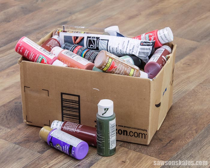 Craft paints in a cardboard box before organizing them in a DIY craft paint storage caddy