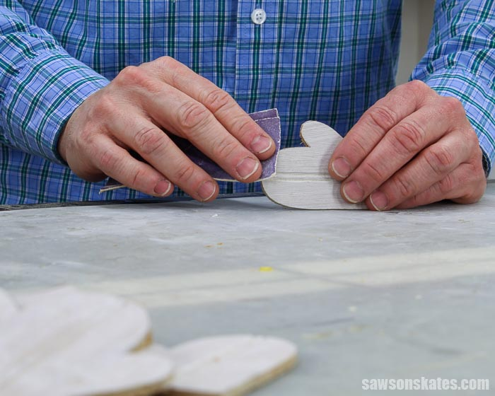 Smoothing the edges of a wood DIY mitten Christmas ornament with sandpaper
