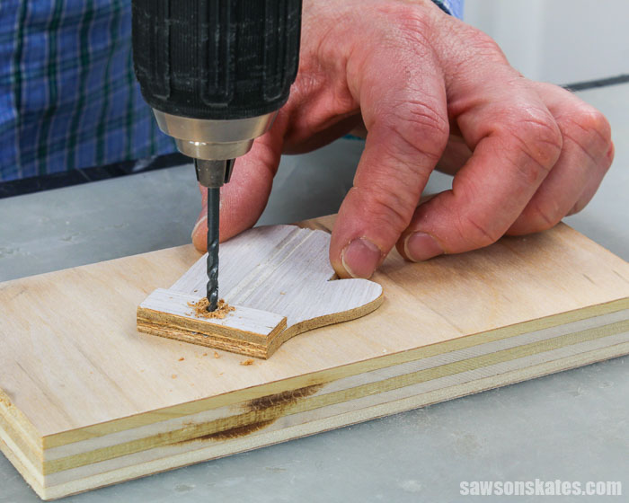 Drilling a hole into a DIY mitten Christmas tree ornament