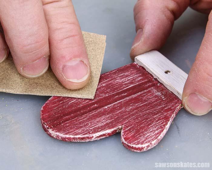 Sanding the paint off a DIY mitten Christmas ornament