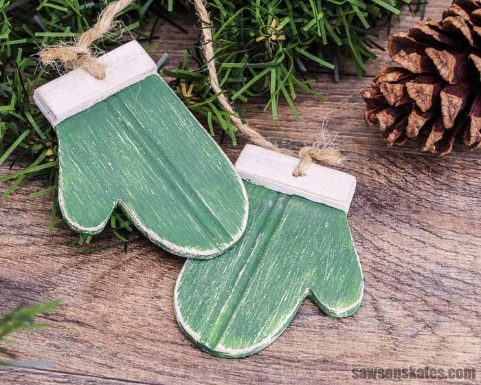 These DIY mitten Christmas ornaments are adorable! They are a quick, easy, and inexpensive afternoon project made with scrap wood, craft paints, and twine.