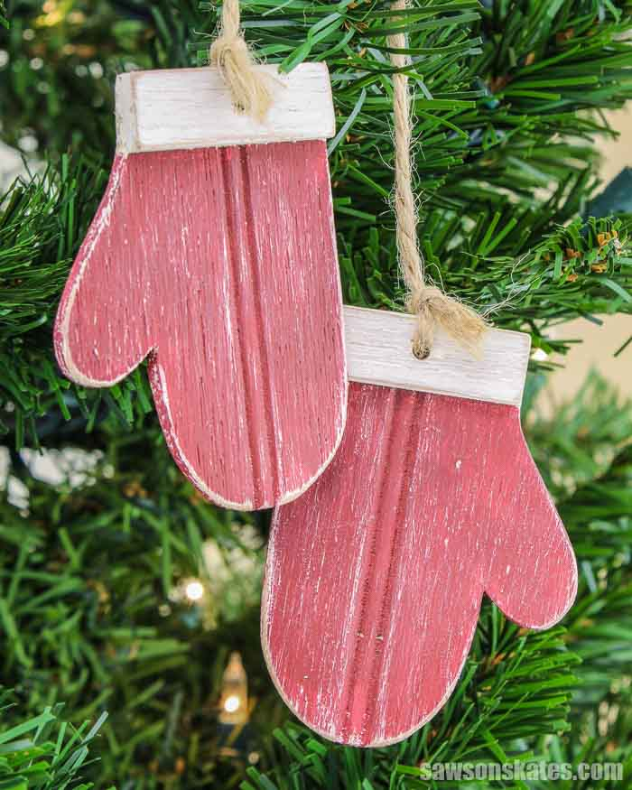 Two red homemade wood mitten ornaments hanging in a Christmas tree