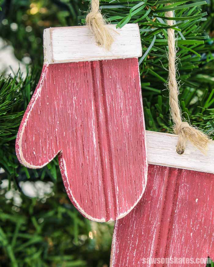 A red homemade wood mitten Christmas ornament hanging in a tree