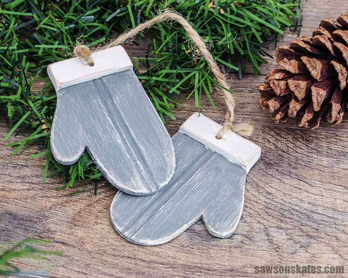 Two grey DIY wood mitten Christmas ornaments with a pine cone