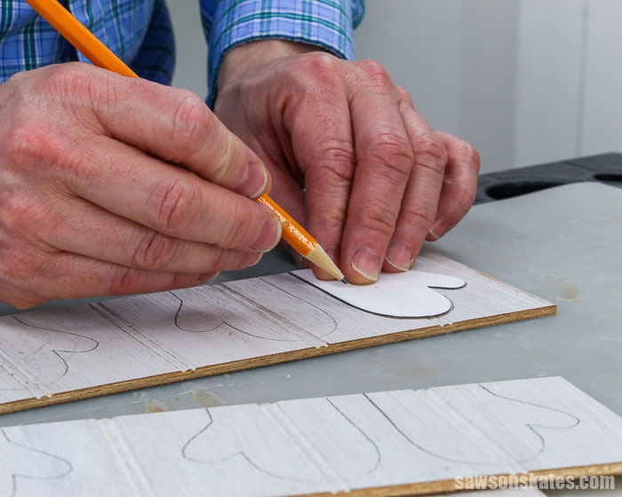 Tracing a mitten Christmas ornament template onto a piece of wood
