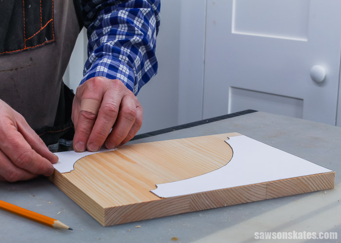 Tracing a template onto a wood blank for small DIY shelf brackets
