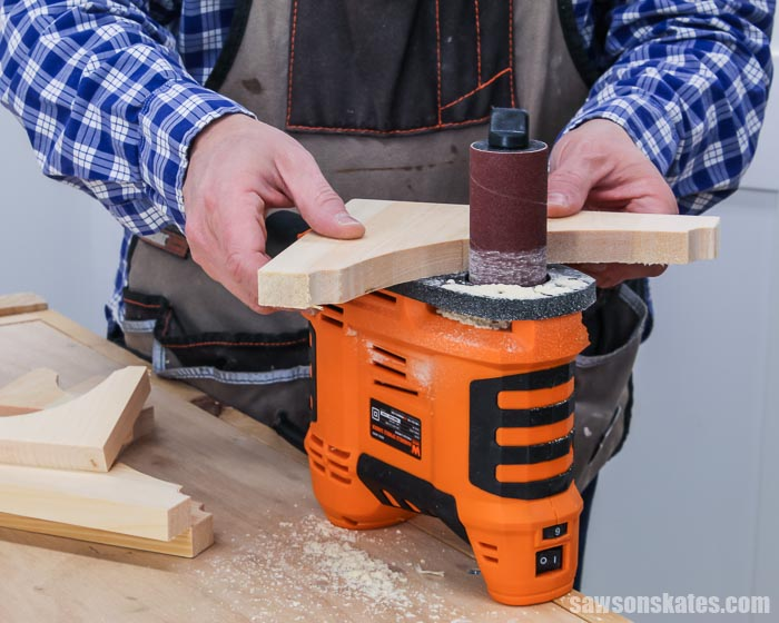 Using a portable spindle sander to smooth the edges of DIY shelf brackets
