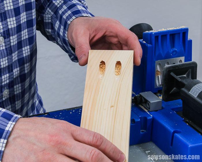 Pocket holes drilled in scrap wood for a DIY shelf bracket
