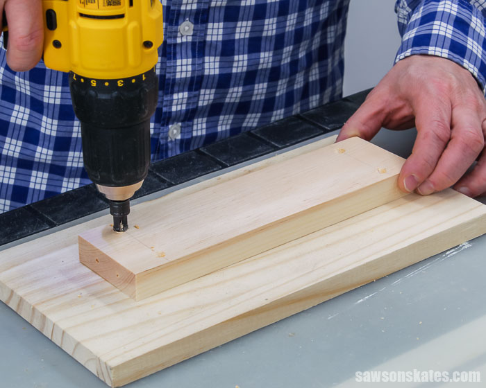 Drilling countersink holes in a piece of scrap wood for a DIY shelf bracket