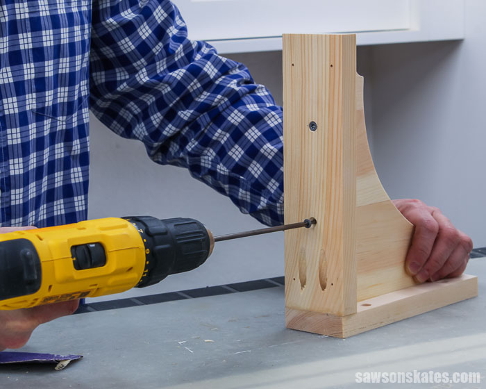 Using a drill to drive a wood screw to assemble wall-mounted DIY shelf brackets