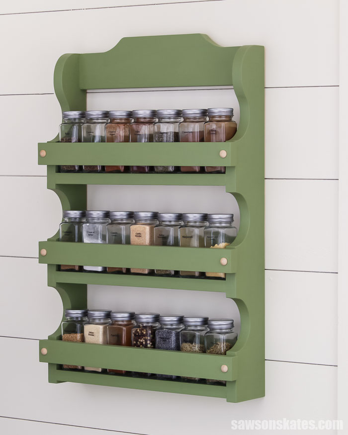 Get your spices organized with this wall-mounted DIY spice shelf. It has three shelves to display spices, and the sides have curvy antique-inspired details.