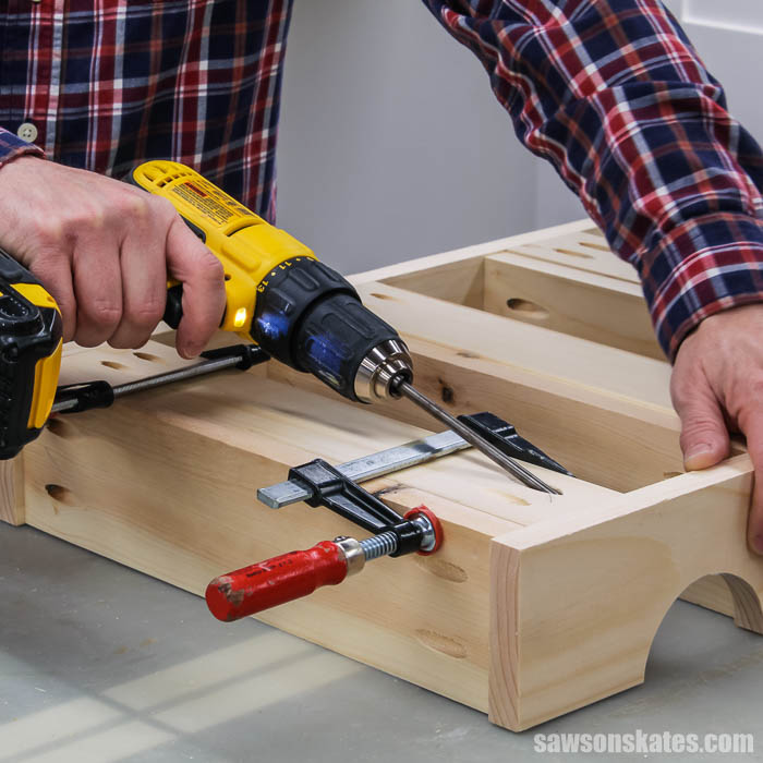 Using a drill to attach the back on a DIY spice shelf