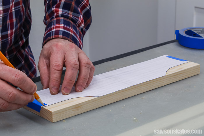 Tracing a template for the top of a wall-mounted DIY spice shelf.