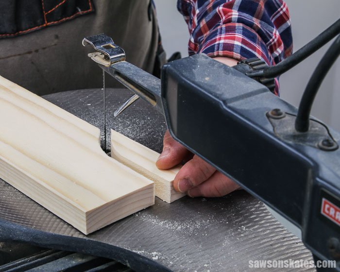 Using a scroll saw to cut the curve detail for the top of a wood DIY spice shelf