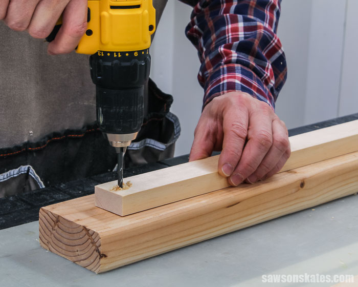 Drilling a pilot hole in a piece of wood for a DIY spice shelf