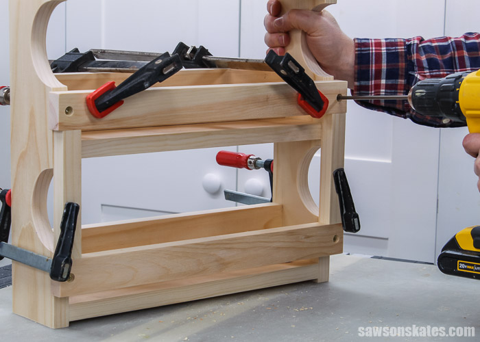 Using a drill to attach the middle rail to a wall-mounted DIY spice shelf