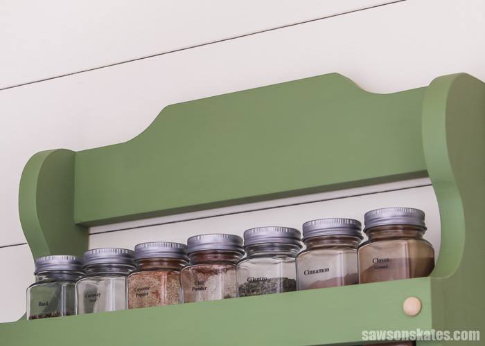 Spice jars and a close up of the curve details at the top of a wall-mounted DIY spice shelf