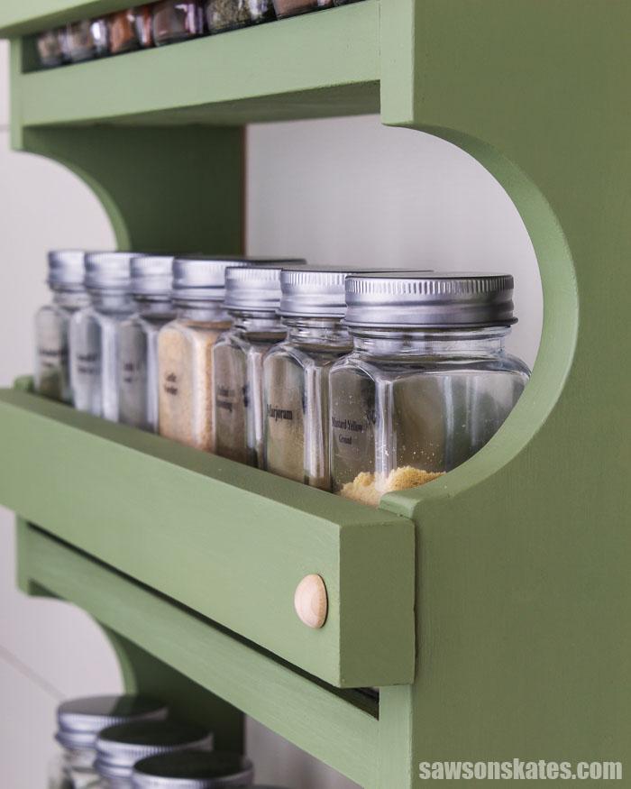 Row of spice jars in a wood DIY spice shelf