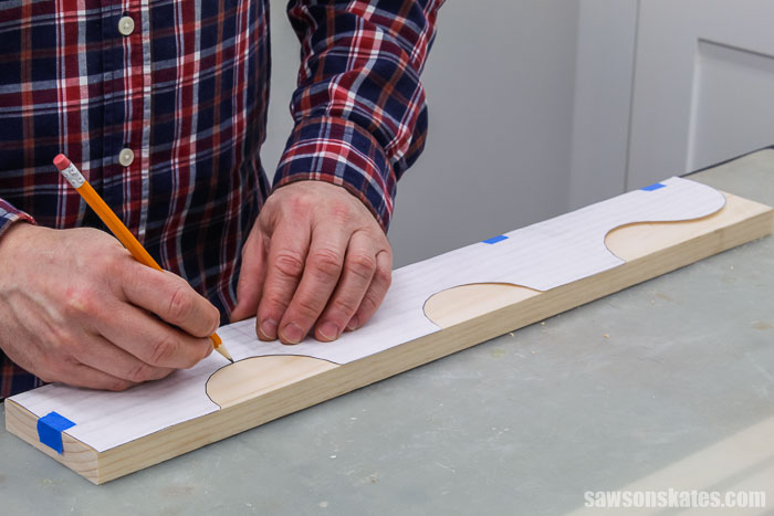 Tracing a template onto a piece of wood for the side of a DIY spice shelf