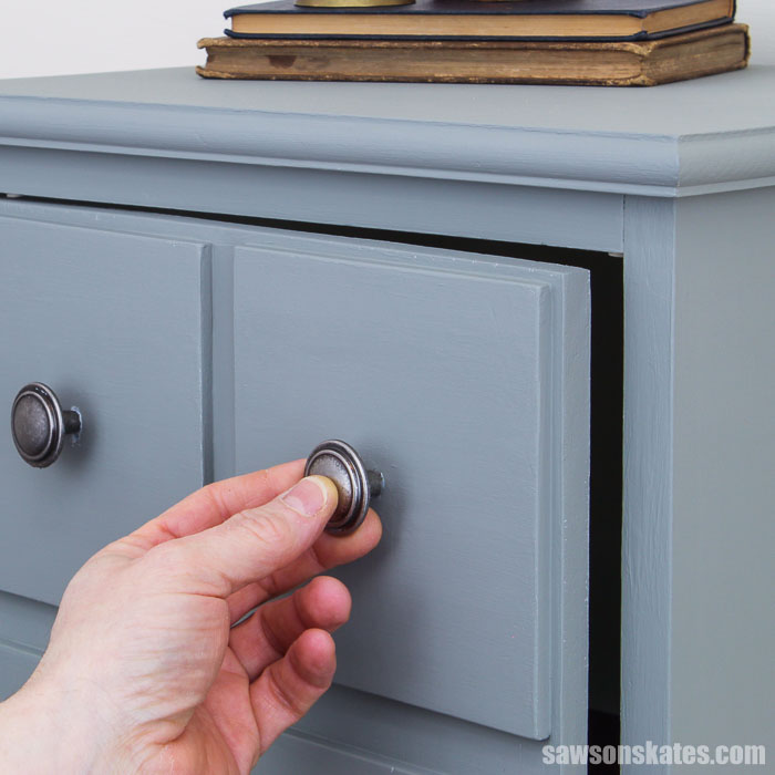 Hand opening the door of a DIY apothecary cabinet