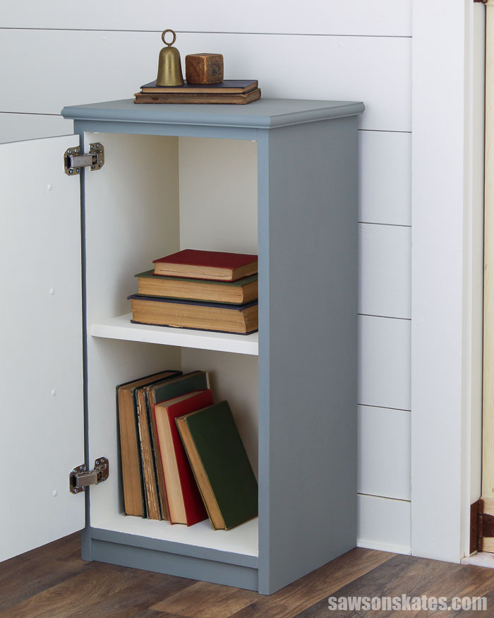 DIY apothecary cabinet with the door open looking inside at the storage area