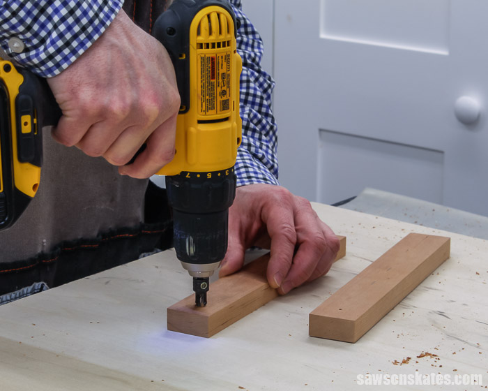 A drill making countersink holes in the frame supports for a tilting DIY wood frame