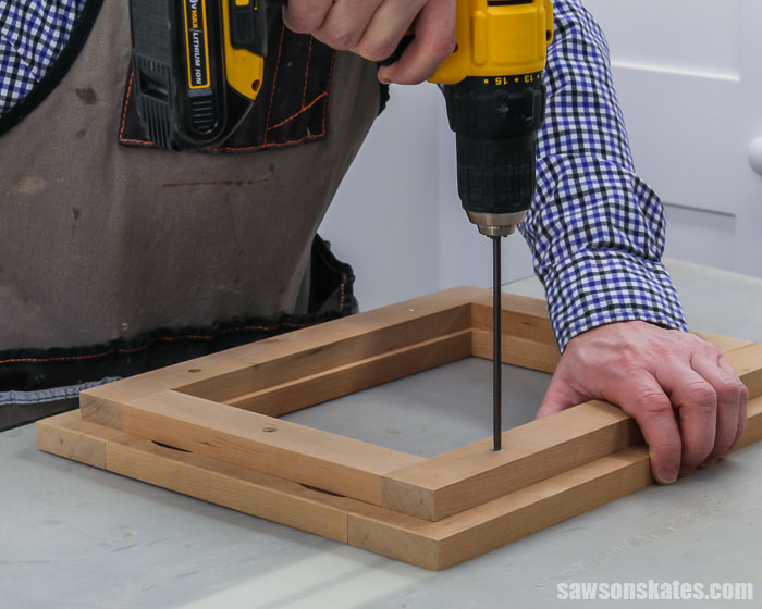 A drill driving screws to attach the glass holder to the face frame for an easy-to-make tilting DIY wood frame