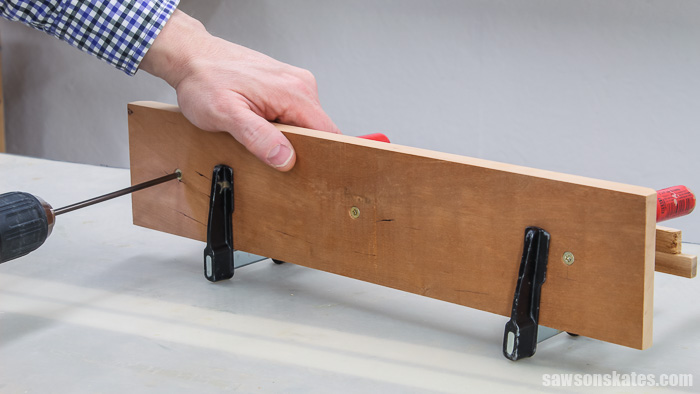 A drill driving screws to attach the lower base to the upper base for a creative tilting DIY wood frame