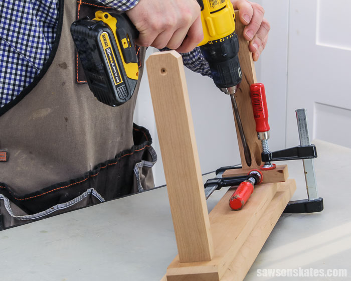 A drill driving pocket screws to attach the frame supports to the base for an easy-to-make tilting DIY picture frame
