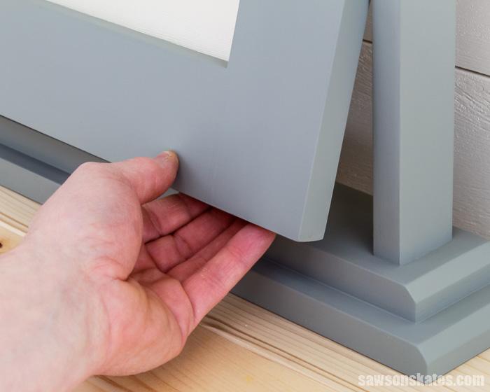 Hand pulling the corner of a tilting DIY wood frame