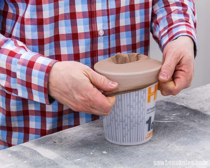 Stretching stockings over a container to use as a paint strainer