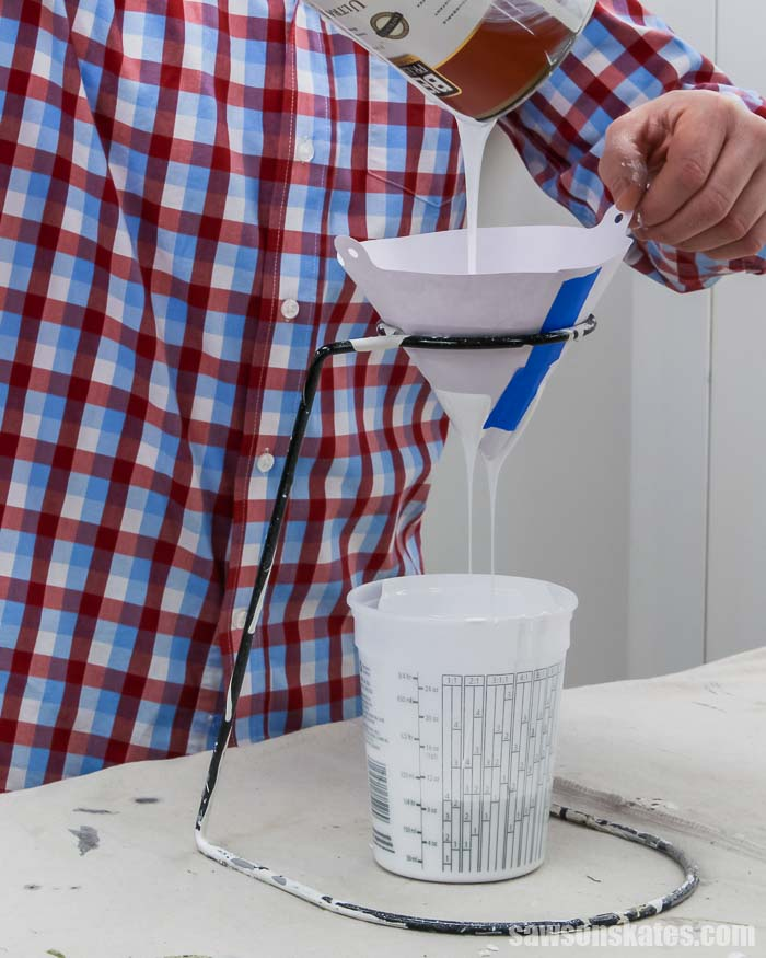 Straining paint through a cone filter into a container