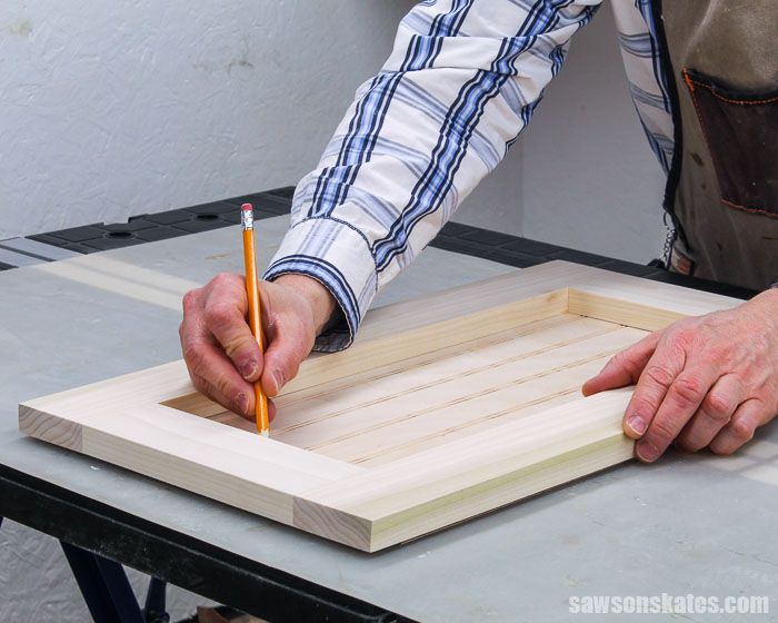Pencil marking the center on a panel for a DIY cabinet door