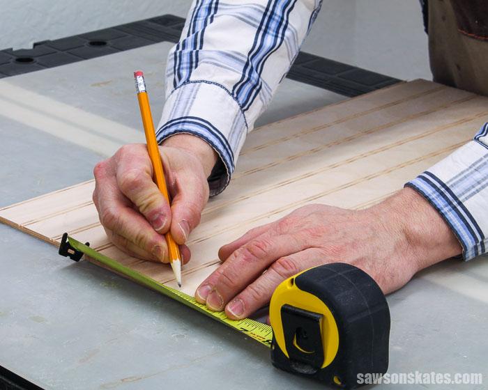 Pencil marking the width of a DIY cabinet door panel