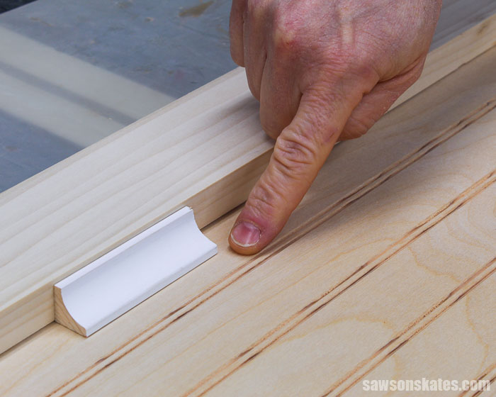 Finger pointing to the space between the molding and beadboard used to make a DIY cabinet door