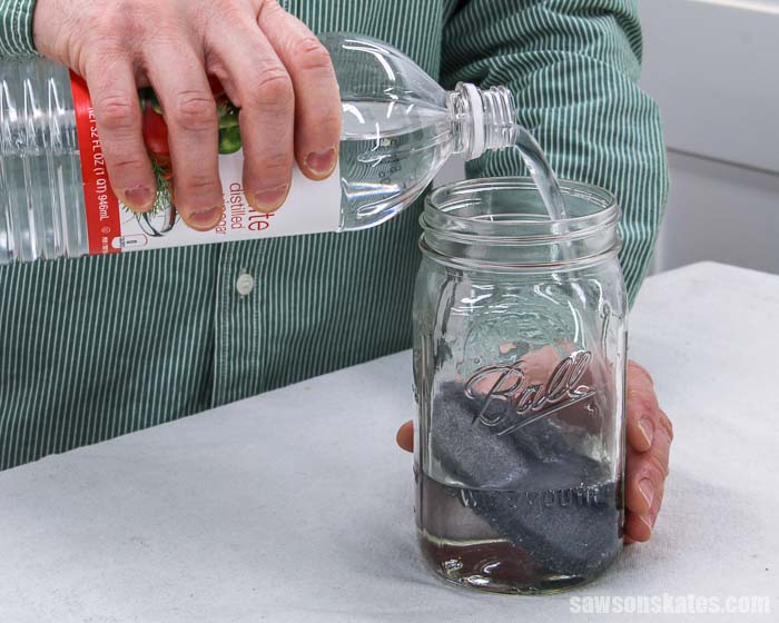 Pouring white vinegar into a mason jar to make vinegar steel wool stain