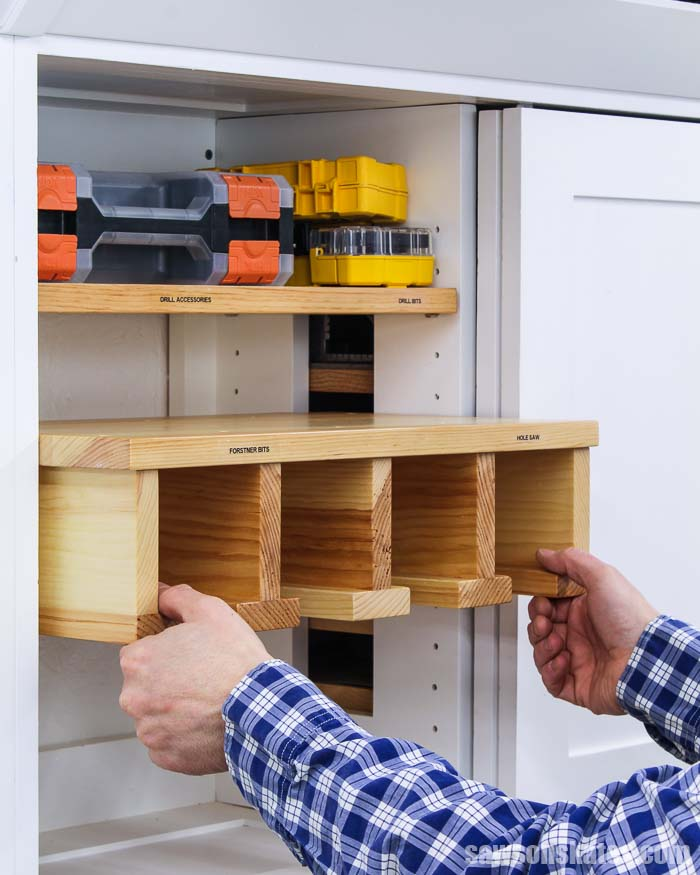 Hands pushing a DIY drill holder into a tool storage cabinet