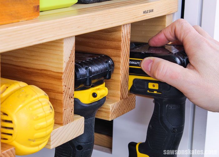Hand removing a drill from a DIY drill holder
