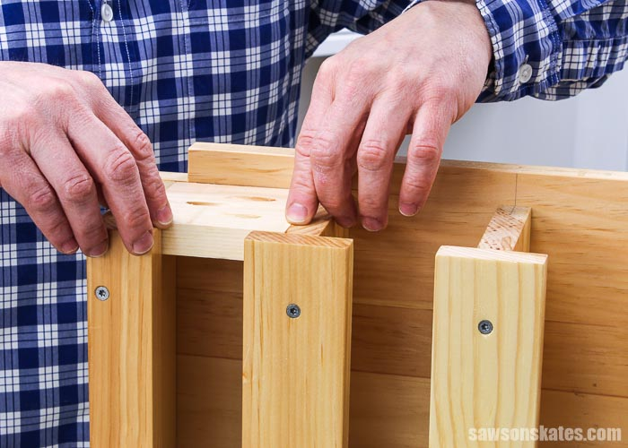 Hands pushing the back into a DIY drill holder