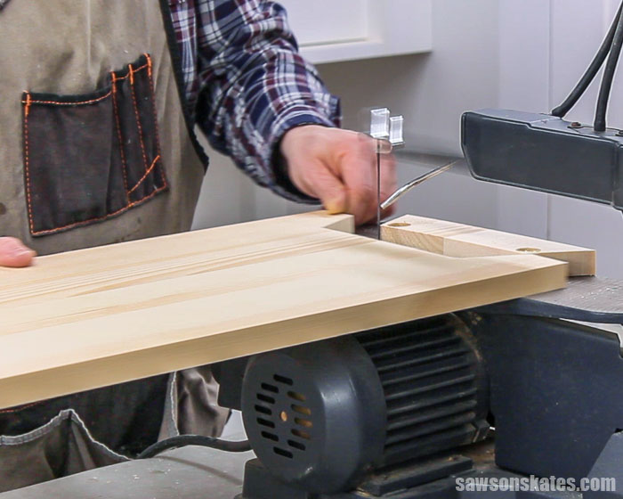 Using a scroll saw to cut the leg detail of a DIY nightstand with three drawers