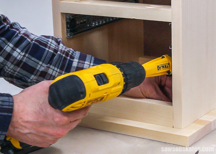Drill attaching the top of a DIY nightstand with drawers