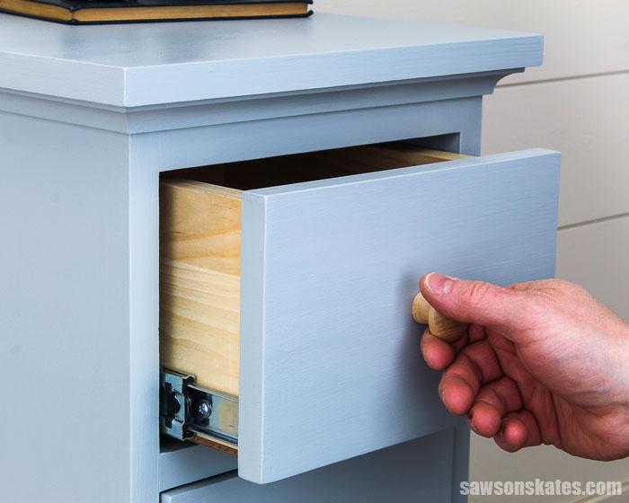 Hand opening the top drawer of a DIY nightstand with three drawers