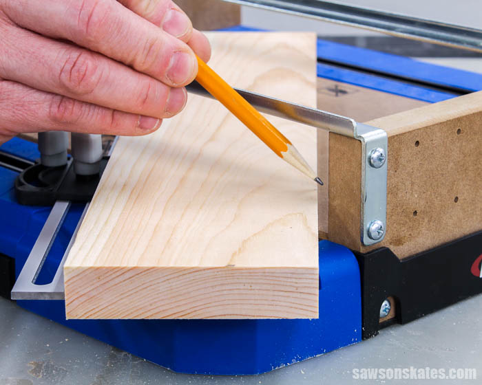 Pencil pointing at the small gap between a 1×4 board and the Kreg Crosscut Station
