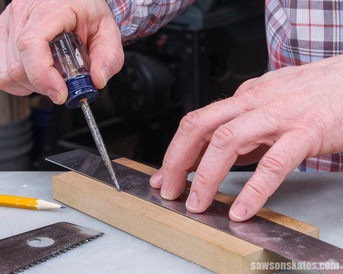 Dragging an awl across a piece of wood to create a scribe line