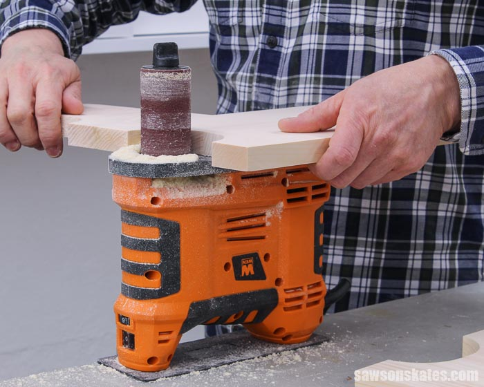 Using a spindle sander to smooth the leg detail of an antique-inspired DIY step stool