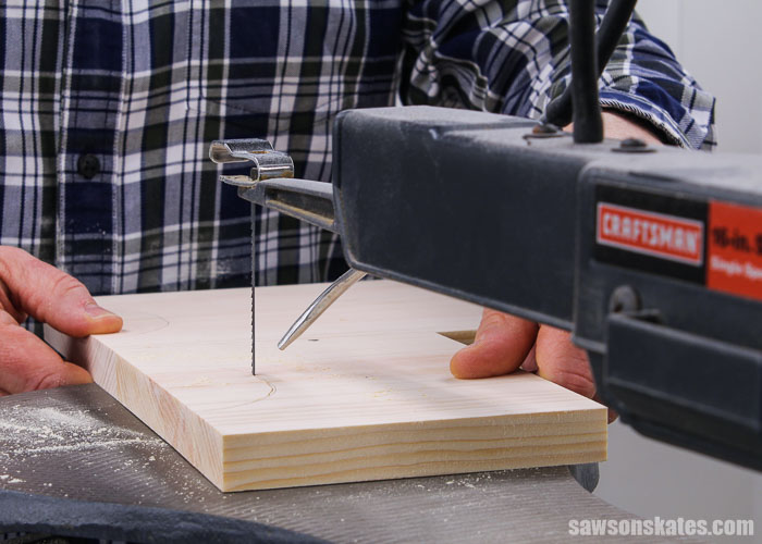 Using a scroll saw to cut out the leg detail of an antique-inspired DIY step stool