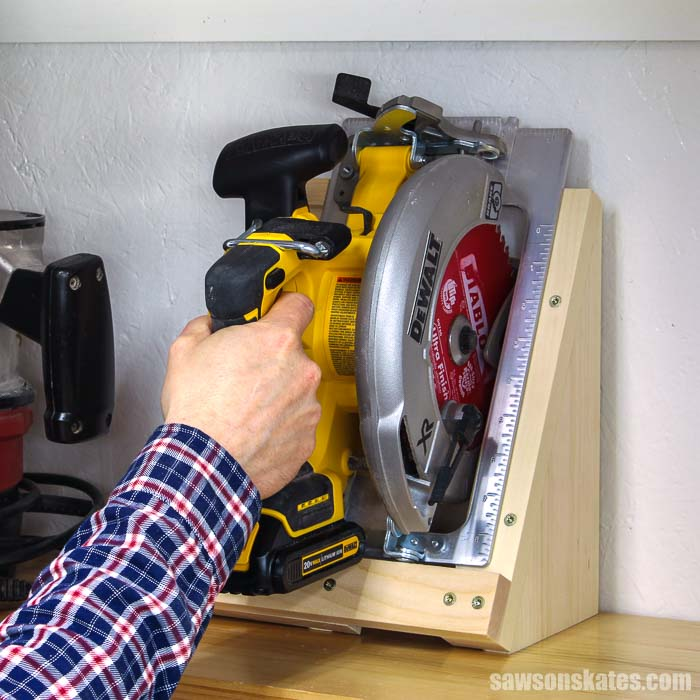 Hand grabbing a saw that is resting on a DIY circular saw storage holder